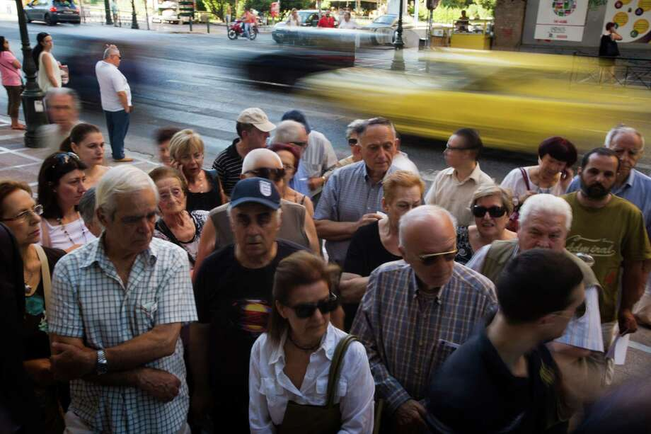 Pensioners wait outside the main gate of the national bank of Greece to withdraw a maximum of 120 euros ($134) in central Athens, Thursday, July 9, 2015. With a deadline just hours away to come up with a detailed economic reform plan, Greece requested a new three-year rescue from its European partners Wednesday as signs grew its economy was sliding toward free-fall without an urgently needed bailout. (AP Photo/Emilio Morenatti) Photo: Emilio Morenatti, STF / AP