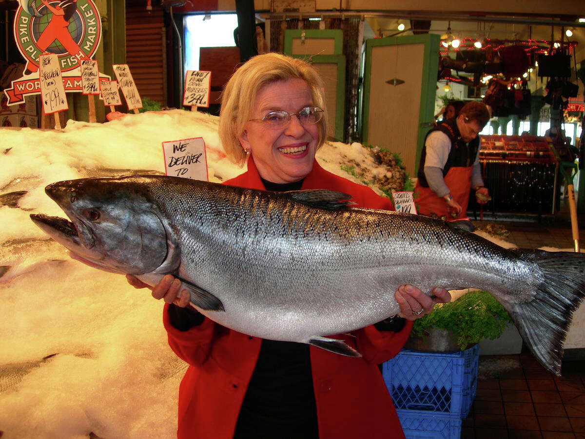 """Seattle City Council member Jean Godden, pictured holding a fish at Pike Place Market on Oct. 3, 2006. The picture adorns cover of her new book """"Citizen Jean."""""""