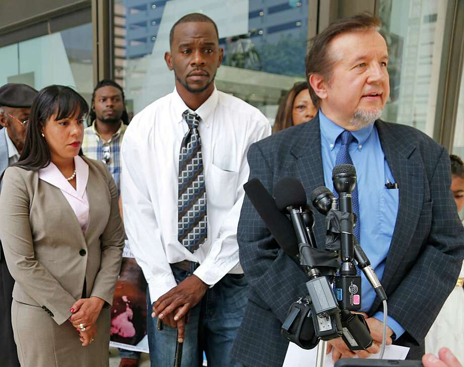 Former truck driver Nicolas Watson stands between his two attorneys  after filing lawsuit against two HPD officers who beat him as he arrived home from work.  Photo: James Nielsen, Staff / © 2015  Houston Chronicle