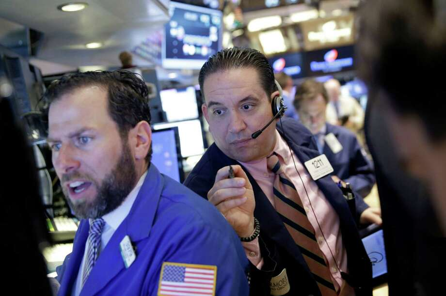 Trader Tommy Kalikas, right, works on the floor of the New York Stock Exchange, Thursday, July 9, 2015  in New York. U.S. stocks opened with big gains, bouncing back from a loss the day before, as investors hoped that last-ditch talks would produce an agreement between Greece and its creditors. (AP Photo/Seth Wenig) ORG XMIT: NYSW106 Photo: Seth Wenig / AP