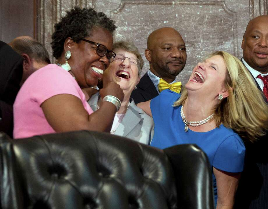 Rep. Gilda Cobb-Hunter, left, laughs with South Carolina Supreme Court Chief Justice Jean Toal, center, and Rep. Jenny Horne, before a ceremony where South Carolina Gov. Nikki Haley signed a bill removing the Confederate Flag from the Statehouse grounds into law Thursday in Columbia.  The law enables the removal of the Confederate flag from the Statehouse grounds more than 50 years after the rebel banner was raised to protest the civil rights movement. (AP Photo/John Bazemore) Photo: John Bazemore, STF / AP