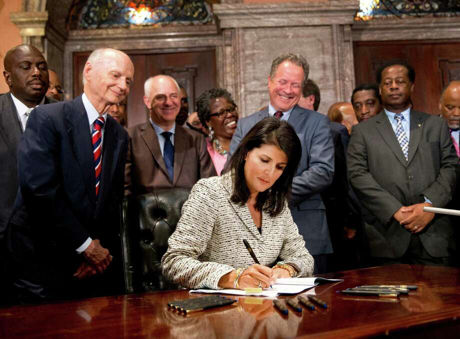 South Carolina Gov. Nikki Haley signs a  law to remove the Confed-erate flag from the Statehouse. grounds July 9, 2015 in Columbia, South Carolina. Debate on the flag was reignited three weeks ago after the mass murder at Emanuel AME Church in Charleston, South Carolina. (Photo by Sean Rayford/Getty Images) Photo: John Bazemore, STF / AP