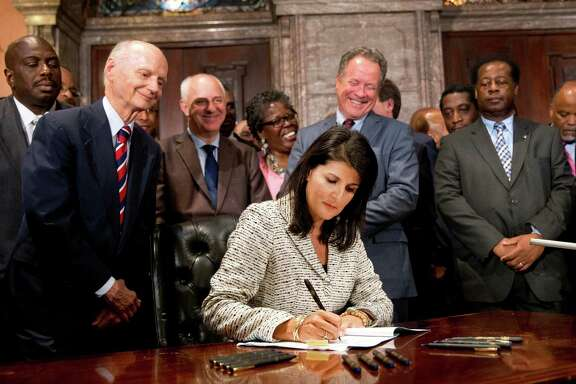 South Carolina Gov. Nikki Haley signs a  law to remove the Confed-erate flag from the Statehouse. grounds July 9, 2015 in Columbia, South Carolina. Debate on the flag was reignited three weeks ago after the mass murder at Emanuel AME Church in Charleston, South Carolina. (Photo by Sean Rayford/Getty Images)