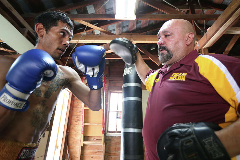 San Antonio professional boxer Ramiro Torres, 33, works out at coach, Joe Ramos, 55, in a backyard gym on the city's south side, Tuesday, June 17, 2015. In spite of a 4-29 record, Torres is determine to achieve a title in his career and has the support of family and Ramos. Photo: Jerry Lara /San Antonio Express-News / © 2015 San Antonio Express-News