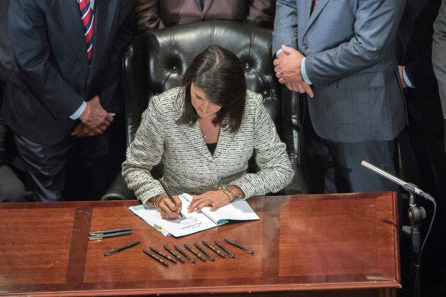 Gov. Nikki Haley signs a bill to remove the Confederate battle flag from the front of the South Carolina State House. The flag is set to come down at 10 a.m. today. Photo: Stephen B. Morton / New York Times / NYTNS