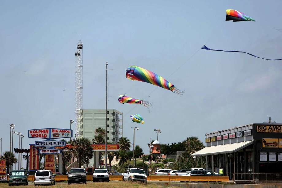 The colorful kites and wind socks outside Kites Unlimited on Seawall Boulevard attract customers to Stephen Newberry's shop. He says complying with the law and removing them would hurt his business. Photo: Gary Coronado, Staff / © 2015 Houston Chronicle