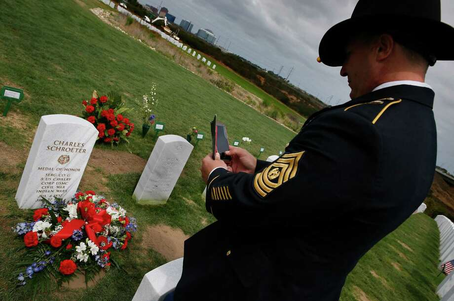 Army Command Sgt. Maj. Gregg Larsen photographs the headstone of Medal of Honor winner Sgt. Charles Schroeter, who was interred Thursday in San Diego.  Photo: Don Bartletti, MBR / Los Angeles Times