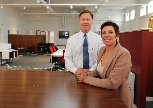 Dorothy Rogers-Bullis, President of DRB Business Interiors, and her husband Dan Bullis, vice president, stand in their business space on Tuesday, June 2, 2015 in Saratoga Springs, N.Y. Rogers-Bullis bought an old Skidmore College building and turned the original theater into a showroom for her business. She also rents two office spaces on the first floor. This photo was taken near what was the stage of the theater. (Lori Van Buren / Times Union) Photo: Lori Van Buren / 00032113A