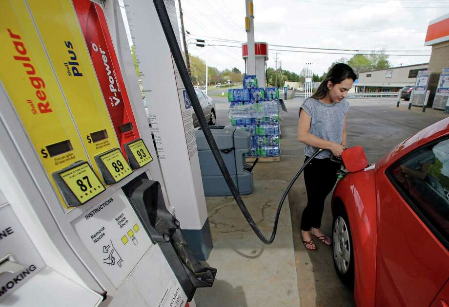 Lucy Perez of Charlotte, N.C., pumps gas at a station in Matthews, N.C.  Prices for U.S. crude sank 13 per-cent from June 30 to Wednesday.  Photo: Chuck Burton, STF / AP
