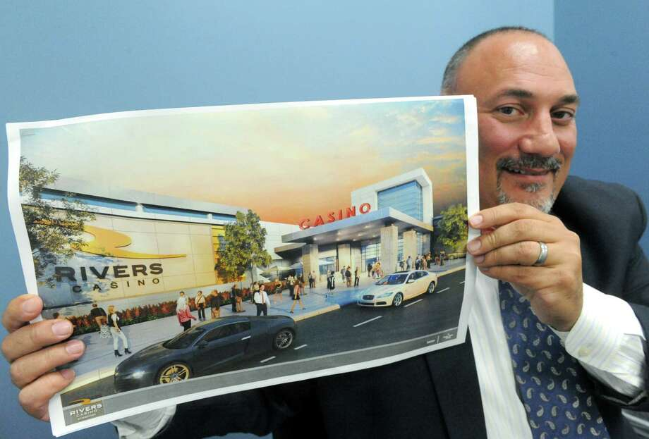 Joe Scibetta, vice president of operations for Rush Street Gaming of Chicago, holds an artists rendering of the new Rivers Casino and Resort to built on the Mohawk River on Thursday July 9, 2015 in Schenectady, N.Y. (Michael P. Farrell/Times Union) Photo: Michael P. Farrell / 00032554A
