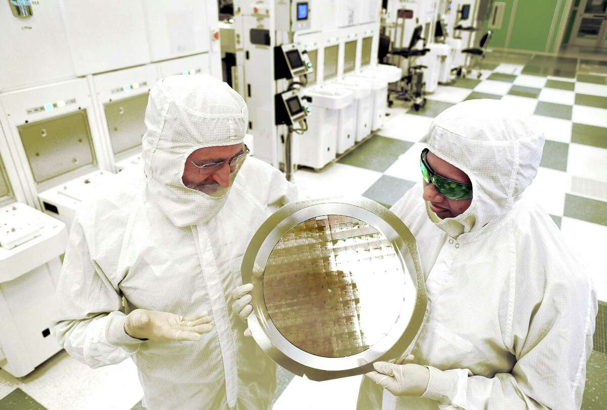 SUNY Polytechnic Institute's Michael Liehr, left, and IBM's Bala Haranand look at wafer comprised of 7nm chips on Thursday, July 2, 2015, in a NFX clean room at SUNY Polytechnic Institute Albany, N.Y. (Darryl Bautista/Feature Photo Service for IBM)