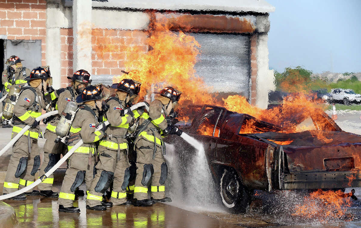 Members of the San Antonio Fire Department Cadet Class 2015 Alpha take part in a live fire demonstration part of the San Antonio Fire Department Cadet Family Night Thursday July 9, 2015 at the SAFD Training Academy. The 23 cadets, who spent the last 5-and-a-half-months training, will graduate on Friday becoming probationary firefighters for 6 months.