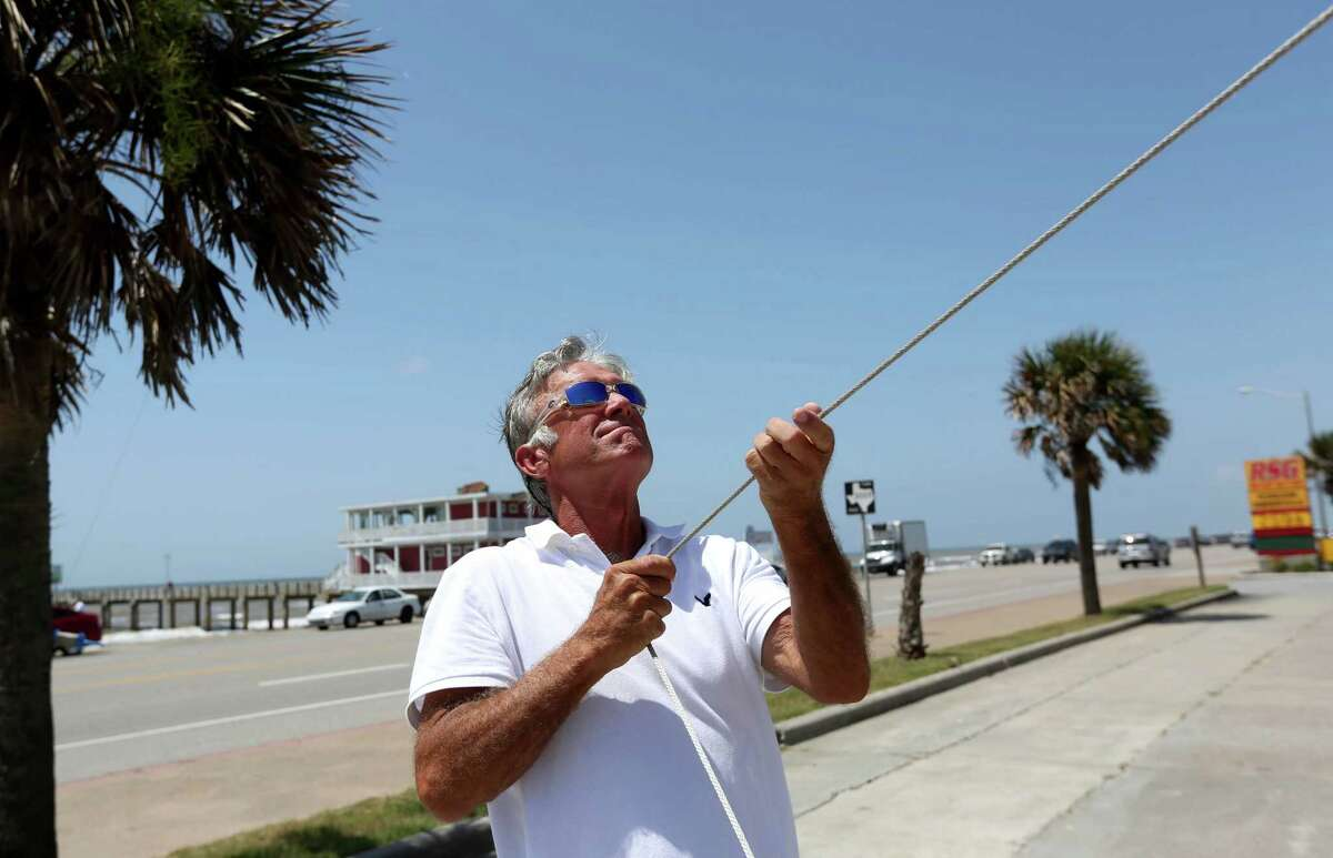 Stephen Newberry, owner, flies a para foil kite to put on display in front of Kites Unlimited Thursday, July 9, 2015, in Galveston, Texas.