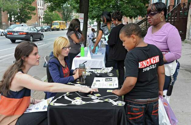 Leah Godin of Rensselaer, left, and Julia Smith of Albany talk to Nicole Hall of Albany and her grandson Justin Scott, 9, about the Words Hurt Heal program during a sidewalk fair to celebrate the new Youth Opportunity Office at 382 Clinton Ave. on Thursday, July 9, 2015 in Albany, N.Y.  (Lori Van Buren / Times Union) Photo: Lori Van Buren / 00032556A