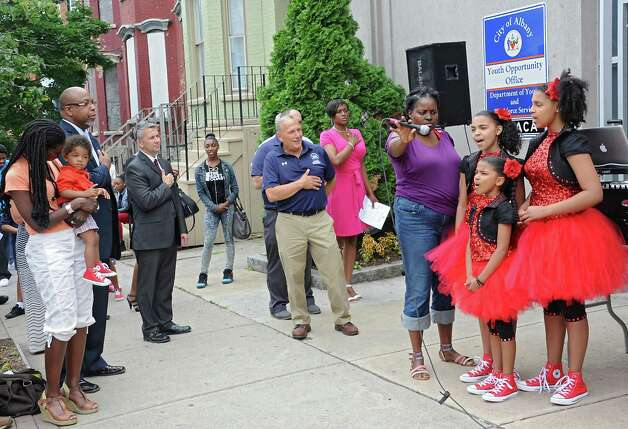 Gennelle Miles of Troy holds the microphone for the singing group Miles-Tone, from left, Alana Miles, 11, Aleah Miles, 8, and Alyssa Miles, 14, all of Troy during a sidewalk fair to celebrate the new Youth Opportunity Office at 382 Clinton Ave. on Thursday, July 9, 2015 in Albany, N.Y. The sisters sang the National Anthem. (Lori Van Buren / Times Union) Photo: Lori Van Buren / 00032556A