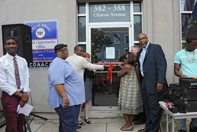 Officials cut a ribbon during a sidewalk fair to celebrate the new Youth Opportunity Office at 382 Clinton Ave. on Thursday, July 9, 2015 in Albany, N.Y.  (Lori Van Buren / Times Union) Photo: Lori Van Buren / 00032556A