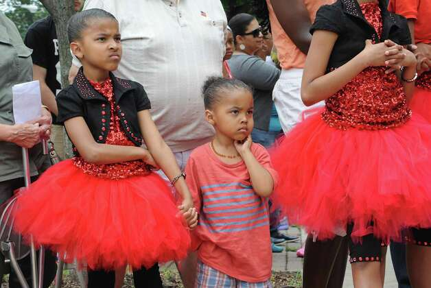 "Aleah Miles,11, of Troy holds the hand of her brother John Miles Jr. ""Junior Bacon,"" 4, during a sidewalk fair to celebrate the new Youth Opportunity Office at 382 Clinton Ave. on Thursday, July 9, 2015 in Albany, N.Y. Their sister Alana Miles, 8, stands at right. (Lori Van Buren / Times Union) Photo: Lori Van Buren / 00032556A"