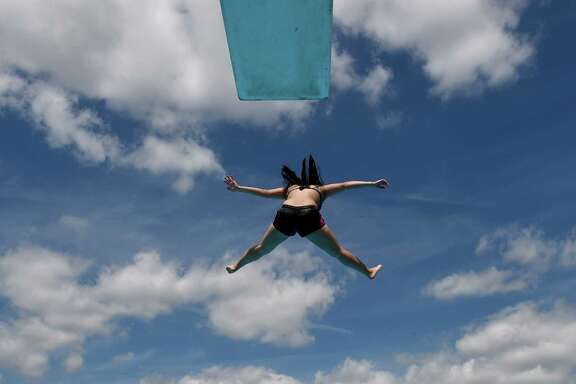 A woman jumps from a diving platform into the water of the public open-air swimming pool in Neumuenster, northern Germany, on June 30, 2015. Meteorologists forecast temperatures across the country of 30 degrees Celsius and even more.     AFP PHOTO / DPA / CARSTEN REHDER   +++    GERMANY OUTCARSTEN REHDER/AFP/Getty Images