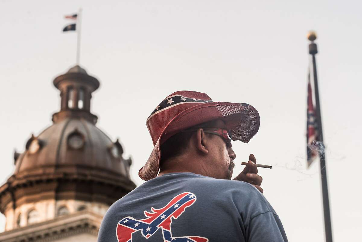 COLUMBIA, SC - JULY 10: John Blankenship watches the sun rise on Confederate battle flag at the South Carolina state house July 10, 2015 in Columbia, SC. Yesterday, Governor Nikki Haley signed a bill ordering the removal of the flag from the capitol grounds this morning at 10 a.m. Blankenship is from Granite Falls, North Carolina. (Photo by Sean Rayford/Getty Images)