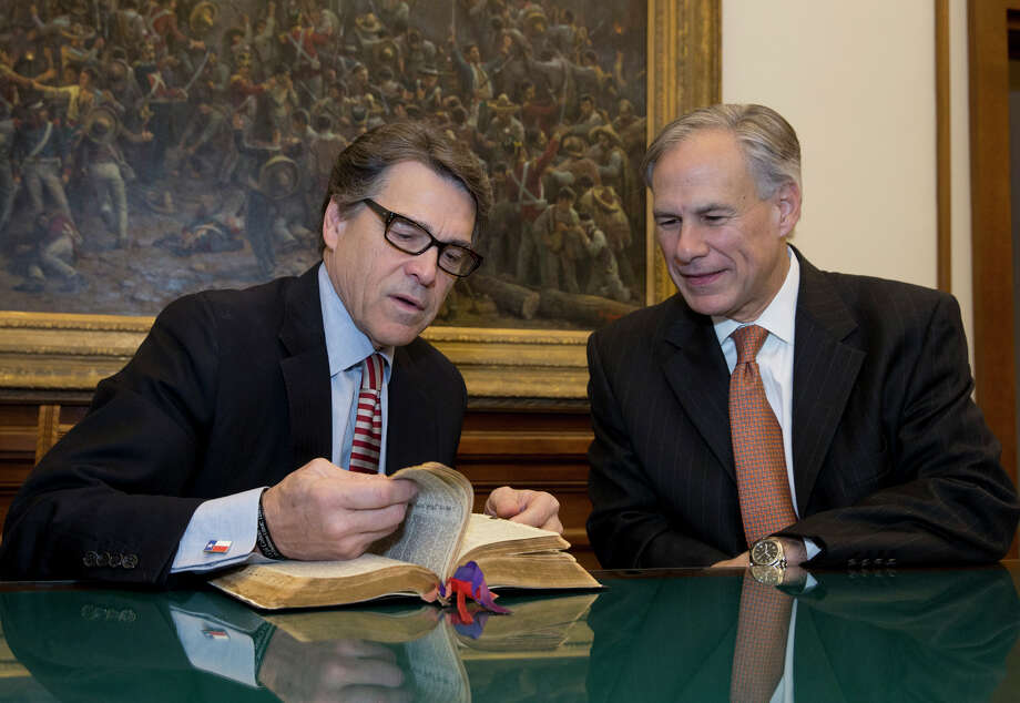 Recent events lead to a disturbing conclusion. There might not be much difference in practice between Texas Gov. Greg Abbott and former Gov. Rick Perry. Here, Perry points out a passage in the Bible that he marked for Abbott, right, prior to the swearing in ceremony at the Capitol Jan 19. Photo: Bob Daemmrich /Associated Press / Pool, Texas Tribune