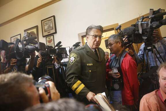 Sheriff Ross Mirkarimi arrives walks through a line of cameras as he arrives at a news conference at San Francisco City Hall on Friday, July 10, 2015 in San Francisco, Calif.