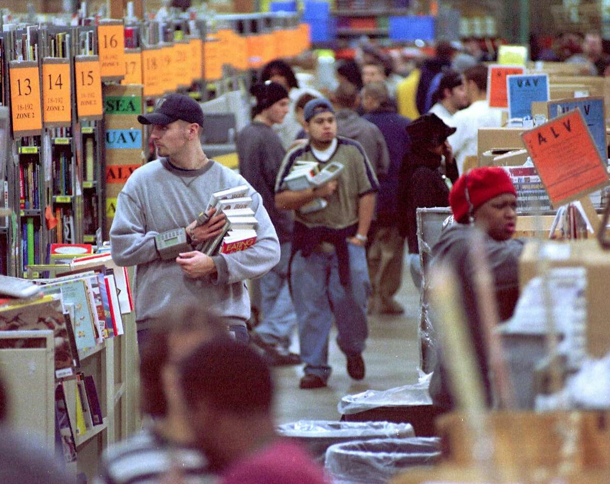 Amazon.com employees fill orders at the company's fulfillment center on Wednesday, December 15, 1999, in Seattle.