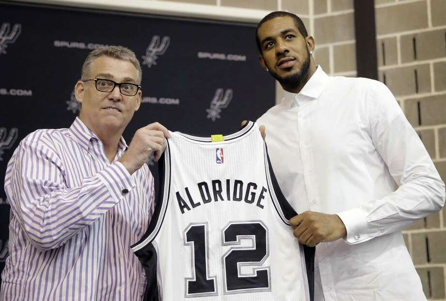 LaMarcus Aldridge, right, poses with San Antonio Spurs general manager R.C. Buford, left, and his new jersey during a news conference at the team's practice facility as he is formally introduced after he signed with the San Antonio Spurs NBA basketball team, Friday, July 10, 2015, in San Antonio. (AP Photo/Eric Gay) Photo: Eric Gay, STF / Associated Press / AP