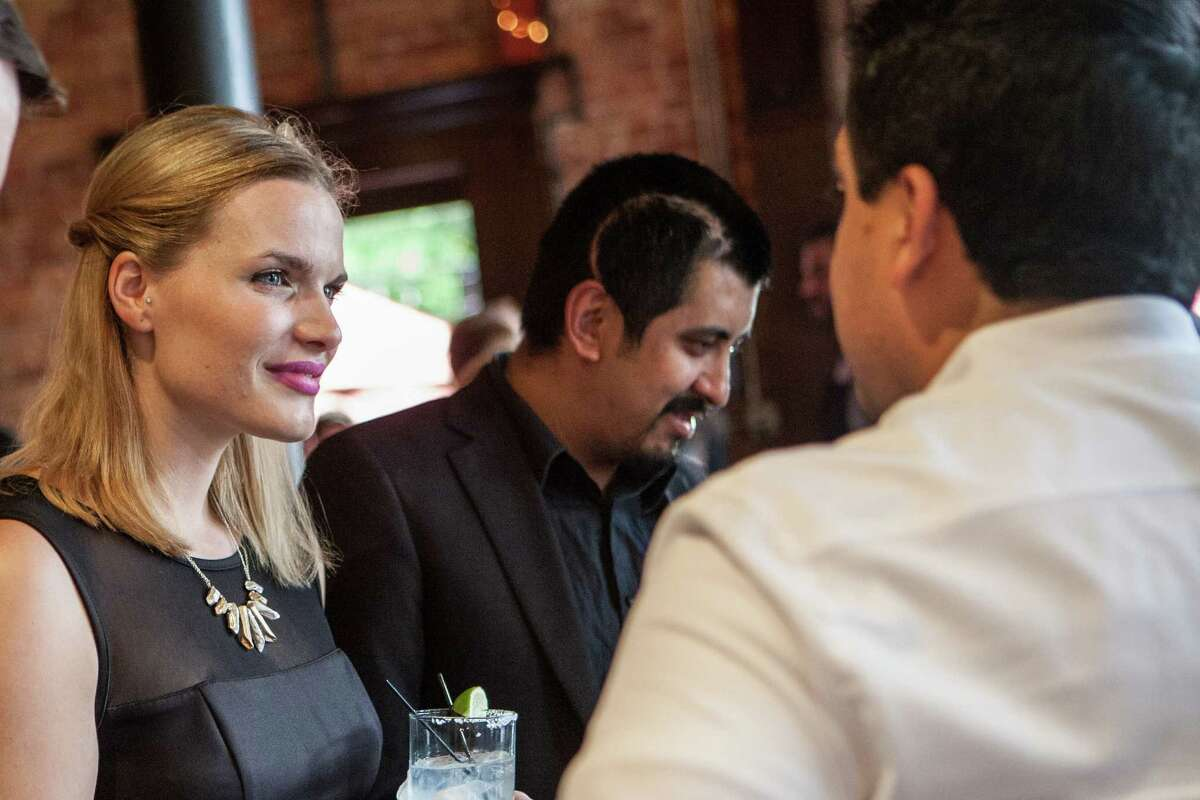 Gillian Givens and her husband, David Guerrero, talk to guests at a fundraiser at Batanga restuarant. Guerrero had recently undergone surgery to remove a second brain tumor, and the fundraiser was being held for him.