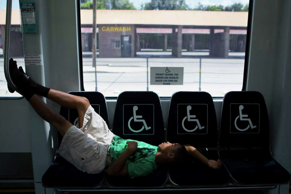 Dashawn Gagnon, 11, gets to be able to stretch taking several sits because the Metro Rail green line is empty, Friday, July 10, 2015, in Houston.