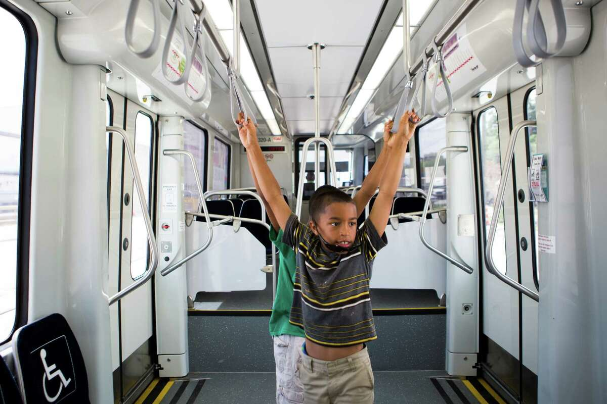 Donte Gagnon, 9, and Dashawn Gagnon, 11, stretch in an empty Metro Green Line train during their ride to downtown Houston on July 10.