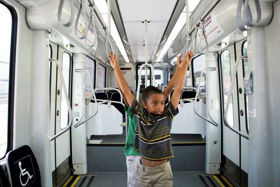 Donte Gagnon, 9, and Dashawn Gagnon, 11, stretch in an empty Metro Green Line railcar during their ride to downtown on Friday. Photo: Marie D. De Jesus, Houston Chronicle / © 2015 Houston Chronicle