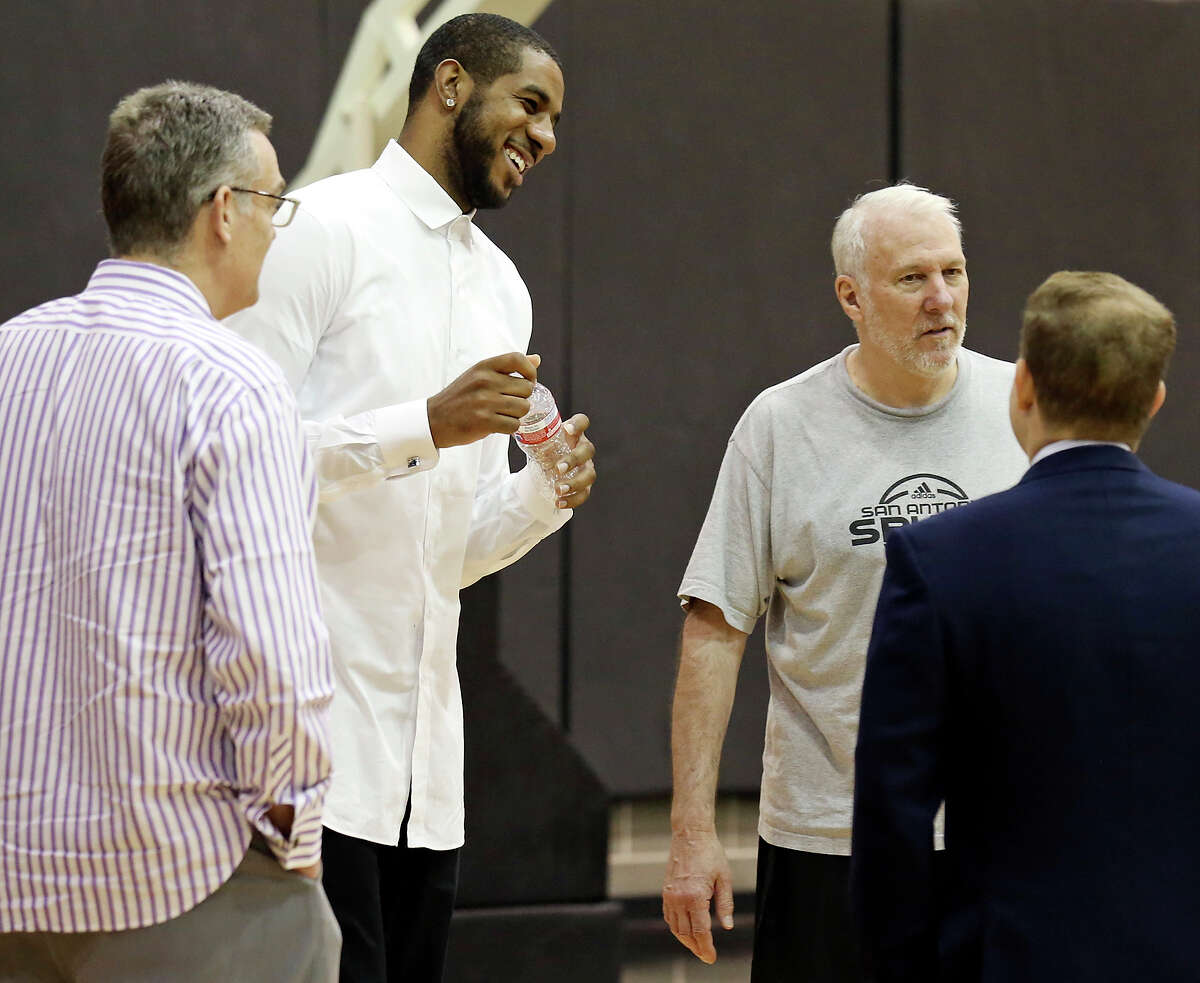 San Antonio Spurs' LaMarcus Aldridge (center) jokes with San Antonio Spurs general manager R.C. Buford (left), head coach Gregg Popovich (center right) and others before a press conference at the Spurs practice facility Friday July 10, 2015 where he was officially introduced.