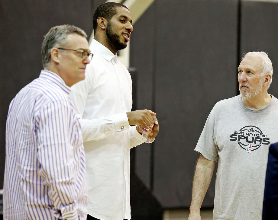 Spurs' LaMarcus Aldridge (center) talks with Spurs general manager R.C. Buford (left), head coach Gregg Popovich and others before a press conference at the practice facility on July 10, 2015. Photo: Edward A. Ornelas /San Antonio Express-News / © 2015 San Antonio Express-News