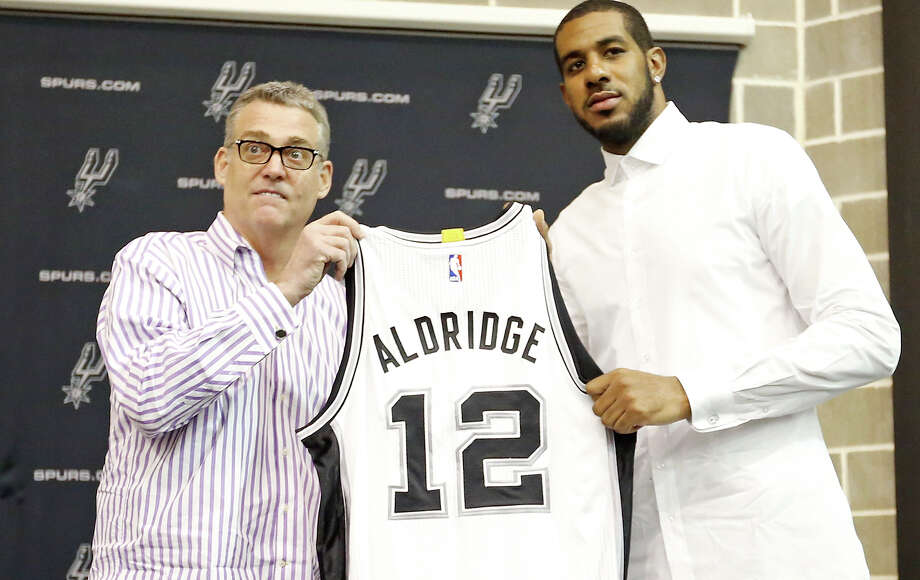 Spurs general manager R.C. Buford and LaMarcus Aldridge pose for photos with Aldridge's jersey during a press conference at the practice facility on July 10, 2015, where he was officially introduced. Photo: Edward A. Ornelas /San Antonio Express-News / © 2015 San Antonio Express-News