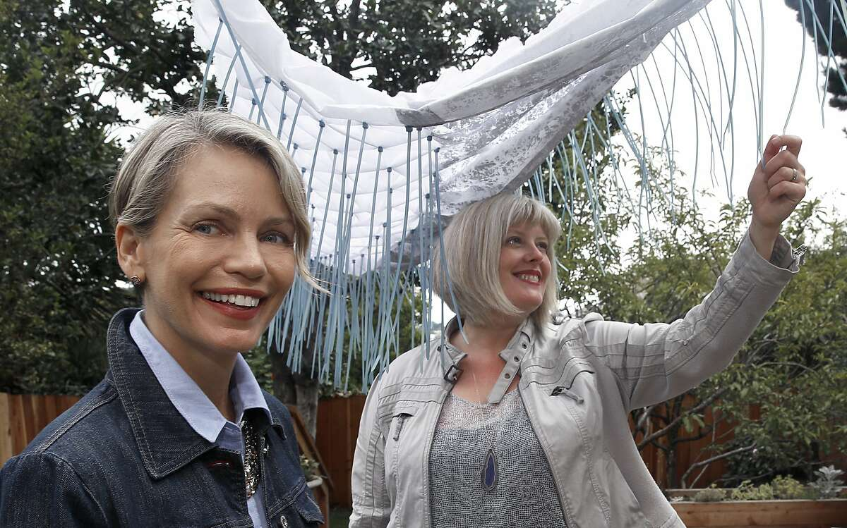 """Textile artist Ealish Wilson (right) and interior designer Anastasia Faiella (left) show a textile piece above in Wilson's backyard in San Francisco, Calif., on Thursday, July 9, 2015. It will be the canopy in a """"water"""" vignette used in a sandy beach scene display at the American Craft Council show at Fort Mason featuring room vignettes inspired by water, earth, air, or fire."""