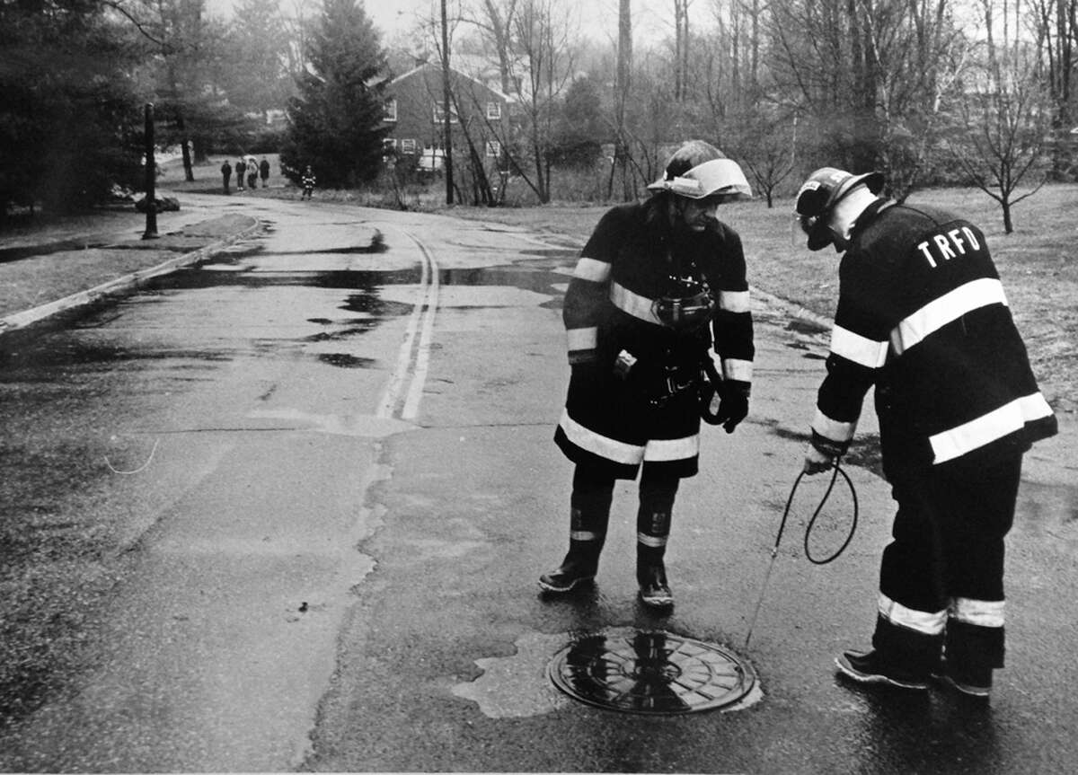 In this photo from 1986, Turn of River Fire Department Deputy Marshall Steve Hellender, right, carrying a gas sniffer, checks out a manhole covers for pockets of natural gas that escaped from a pipe vent. At left is Firefighter Don King. The gas leak closed area streets and Sunday School classes at the Newfield School were asked to go home early.