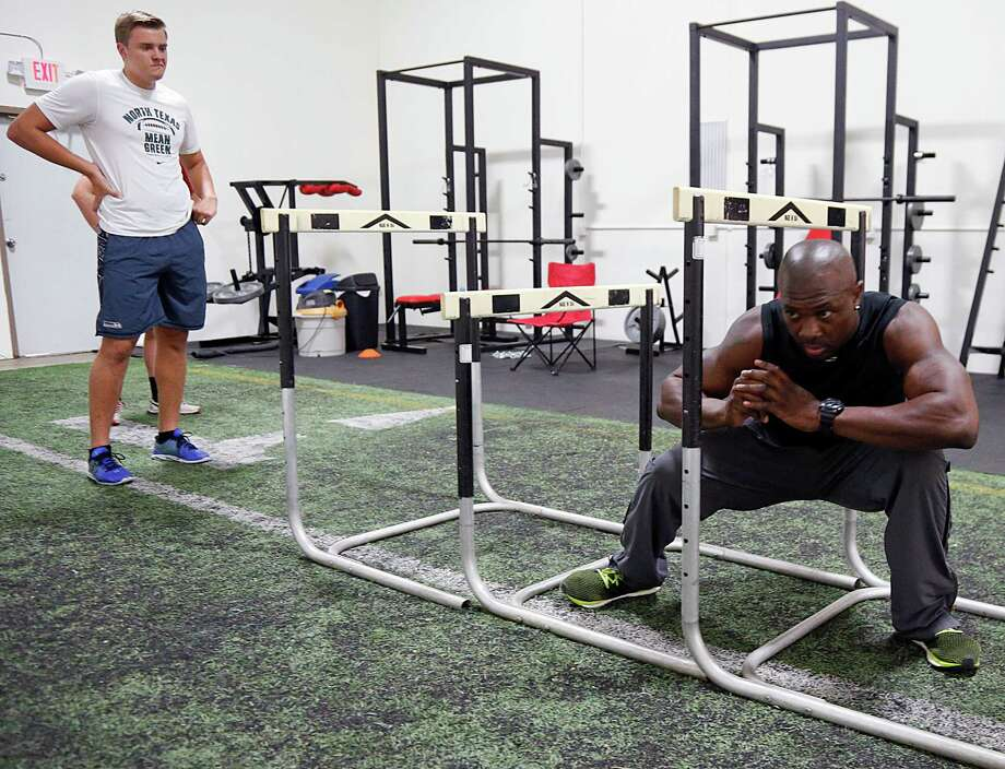 Eddie Jackson Jr., right, demonstrates an exercise for client Jackson Solbeck at Fit Chef Studio. Photo: James Nielsen, Staff / © 2015  Houston Chronicle