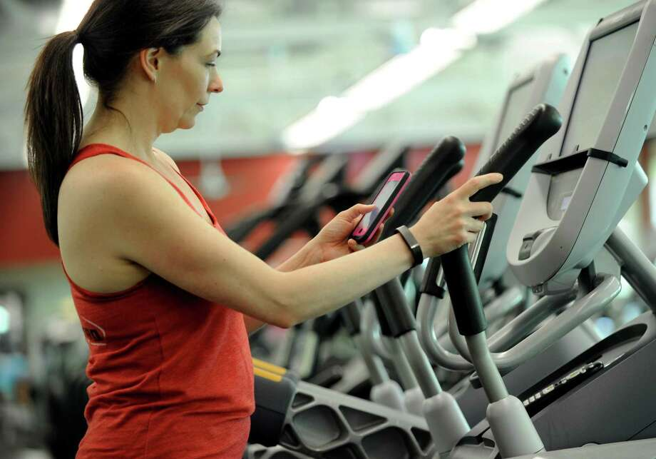 Suzette Caldwell, of New Milford, uses the FitBit app on her smartphone while on an elliptical machine at the New Milford Sports Club on Friday. Photo: Carol Kaliff / Hearst Connecticut Media / The News-Times