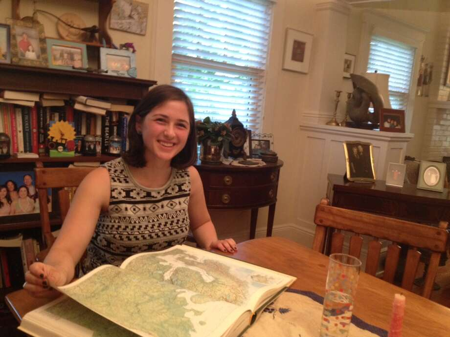 Ashley Braunthal brushes up on the geography of Scandinavia at her home in Riversides. She will spend a year in the region studying climate science. Photo: / Robert Marchant / Greenwich Time