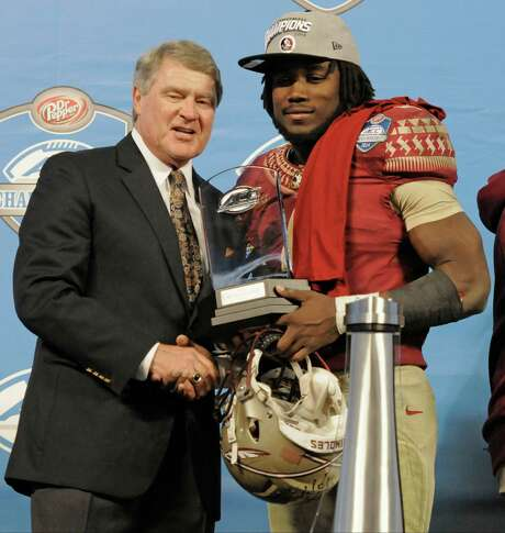 Florida State's Dalvin Cook, right, receives the MVP trophy from commissioner John Swofford, left, after winning the Atlantic Coast Conference championship NCAA college football game in Charlotte, N.C., Saturday, Dec. 6, 2014. Florida State defeated Georgia Tech 37-35. (AP Photo/Mike McCarn) Photo: Mike McCarn, FRE / FR34342 AP