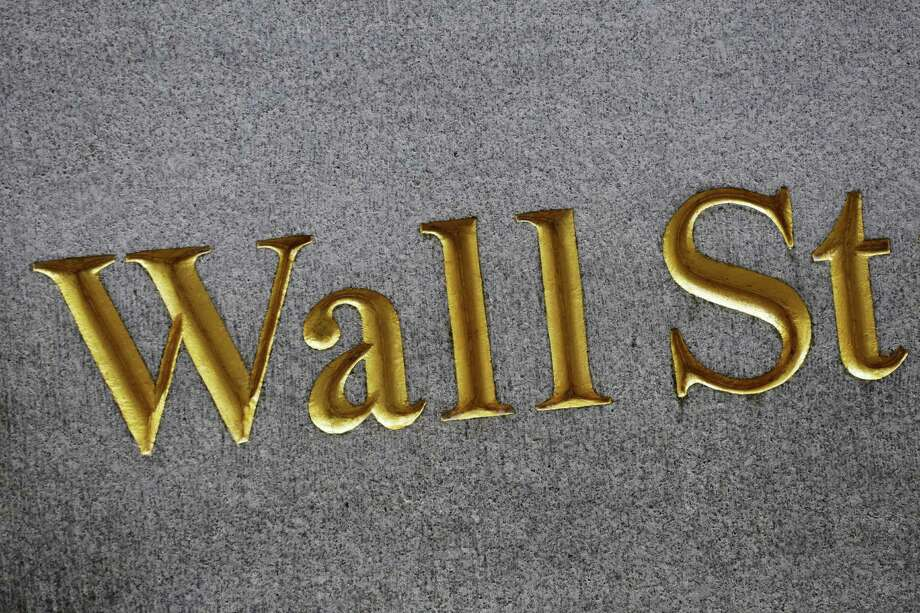 This Monday, July 6, 2015 photo shows a sign for Wall Street carved into the side of a building, in New York. Hopes that Greece will be able to forge a deal with creditors this weekend that will secure its euro future helped stock markets around the world and Europe's single currency itself post big gains on Friday, July 10. (AP Photo/Mark Lennihan) ORG XMIT: NYSB501 Photo: Mark Lennihan / AP