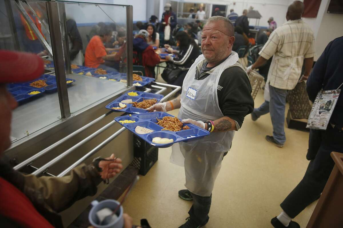 """Volunteer John """"Racoon"""" Callahan serves diners during the evening meal at Glide Memorial on Thursday, July 9, 2015 in San Francisco, Calif."""