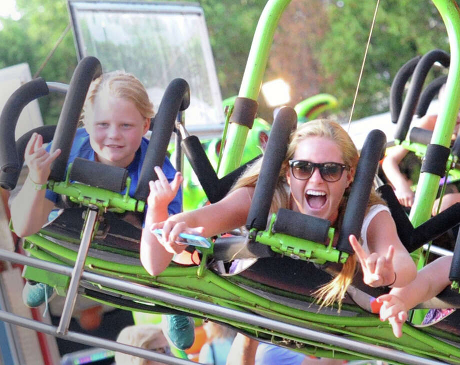 At right, Jenny Goggin of Geenwich screams while riding the Star Flyer during the St. Catherine of Siena Church annual Carnival of Fun at the church in the Riverside section of Greenwich, Conn., Friday night, July 10, 2015. Photo: Bob Luckey Jr. / Hearst Connecticut Media / Greenwich Time
