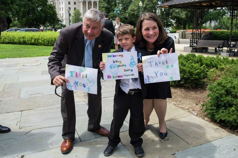 Max Schill, 6, shows off his thank-you signs Friday with Reps. Fred Upton and Diana DeGette at the Capitol in Washington after passage of a health bill. Photo: ZACH GIBSON, STF / NYTNS