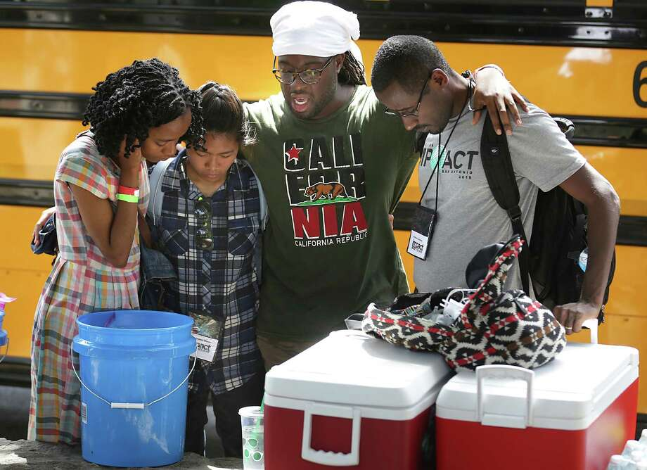 Members of IMPACT, The 7th Day Adventist Outreach Program, Peo Tauetsile, from left, Jesha Munez, Xavyance Handfield, and Getahun Lombamo, pray before they head out to distribute water and personal hygiene packets to the homeless on Thursday, July 9, 2015, near Haven for Hope. Photo: Bob Owen, Staff / San Antonio Express-News / ©2015 San Antonio Express-News