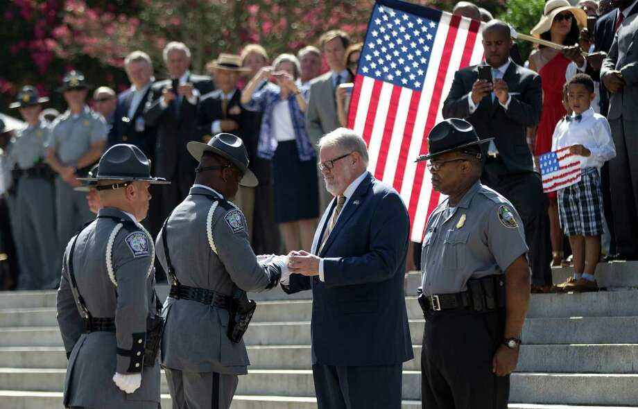 A member of the honor guard from the South Carolina Highway Patrol that removed the Confederate battle flag that flew in front of the Statehouse hands it over to the curator of the Confederate Relic Room and Military Museum after it was taken down Friday in Columbia, S.C.  (AP Photo/John Bazemore) Photo: John Bazemore, STF / AP