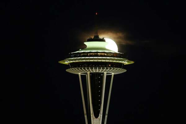 The nearly full moon rises behind the Space Needle as seen on Thursday, July 2, 2015.