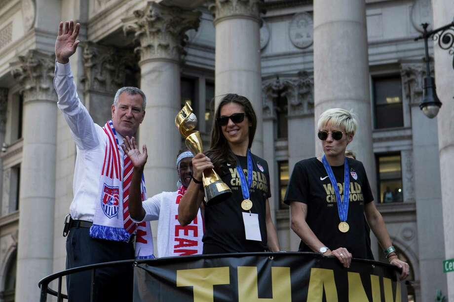 Carli Lloyd holds the World Cup trophy as she and other members of the U.S. womené¢Â€Â™s national soccer team paraded down Broadway in New York, July 10, 2015. Ité¢Â€Â™s the first time the city has honored a womené¢Â€Â™s sports team with a ticker-tape parade. At left is Mayor Bill de Blasio, at right, Megan Rapinoe. (Mark Kauzlarich/The New York Times) Photo: MARK KAUZLARICH, STF / NYTNS