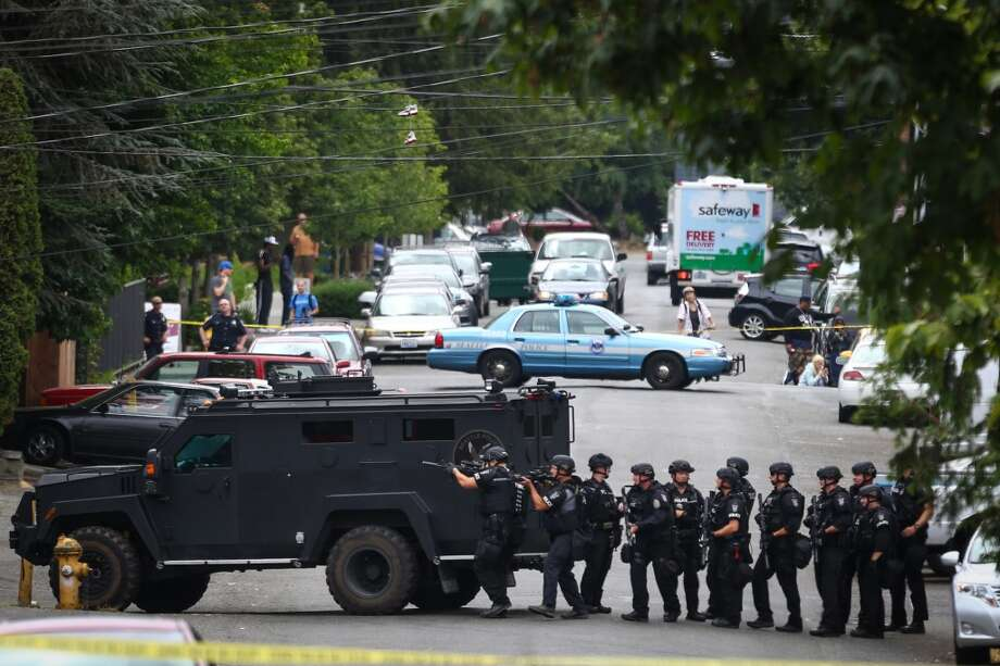 Seattle Police SWAT officers move in after a shooting on 32nd Avenue Northeast left one man injured and others that may have been involved in the shooting holed up in a nearby apartment building. Photographed on Friday, July 10, 2015. Photo: JOSHUA TRUJILLO, SEATTLEPI.COM