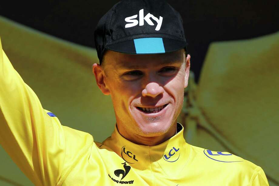 Britain's Christopher Froome, wearing the overall leader's yellow jersey, celebrates on the podium of the seventh stage of the Tour de France cycling race over 190.5 kilometers (118.4 miles) with start in Livarot and finish in Fougeres, France, Friday, July 10, 2015. (AP Photo/Laurent Cipriani) ORG XMIT: PDJ142 Photo: Laurent Cipriani / AP